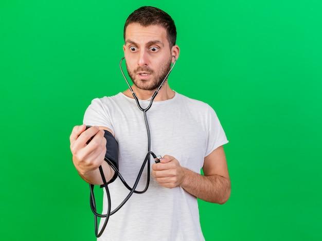 Spaventato giovane uomo malato che misura la propria pressione con sfigmomanometro isolato su sfondo verde