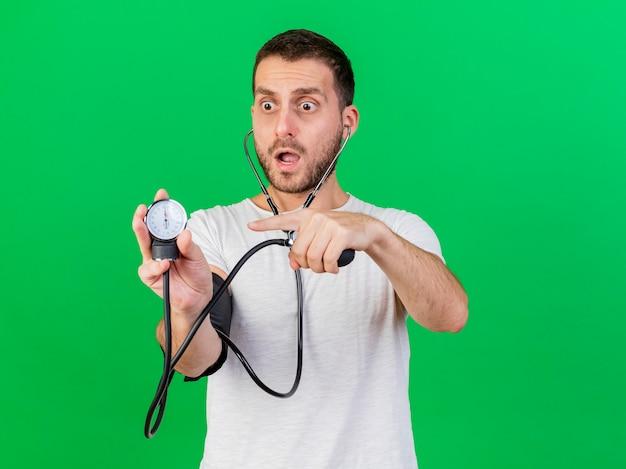 Испуганный молодой больной человек со стетоскопом держит и указывает на сфигмоманометр, изолированный на зеленом фоне