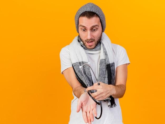 Испуганный молодой больной человек в зимней шапке и шарфе держит и надевает стетоскоп на руку, изолированную на желтом