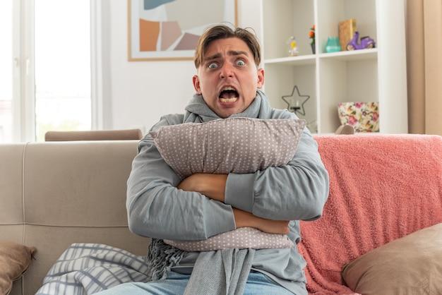 Spaventato giovane uomo malato con sciarpa intorno al collo abbracciando cuscino seduto sul divano in soggiorno