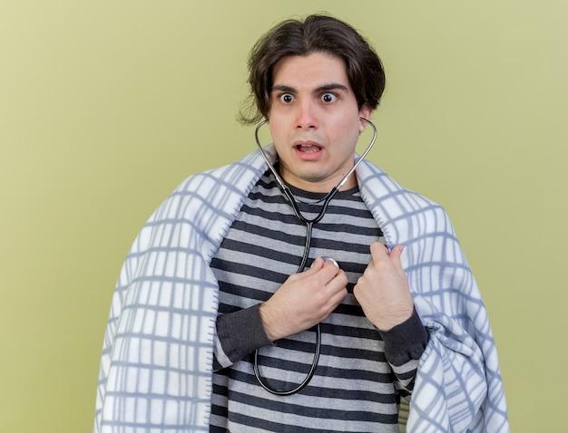 Spaventato giovane uomo malato avvolto in un plaid che indossa e ascolta il proprio battito cardiaco con lo stetoscopio isolato su sfondo verde oliva