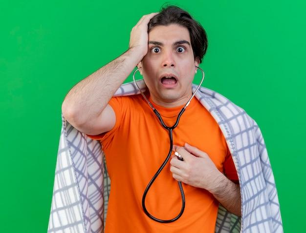 Spaventato giovane uomo malato avvolto in un plaid che indossa e ascolta il proprio battito cardiaco con lo stetoscopio mettendo la mano sulla testa isolata su sfondo verde