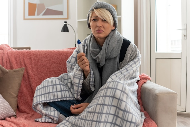 Spaventata giovane donna slava malata con sciarpa intorno al collo avvolto in plaid che indossa cappello invernale tenendo il termometro seduto sul divano in soggiorno