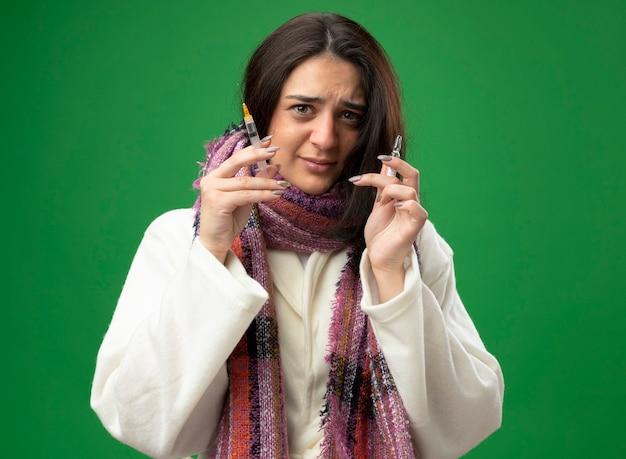 Spaventata giovane donna malata che indossa accappatoio e sciarpa tenendo la fiala e la siringa guardando la parte anteriore isolata sulla parete verde