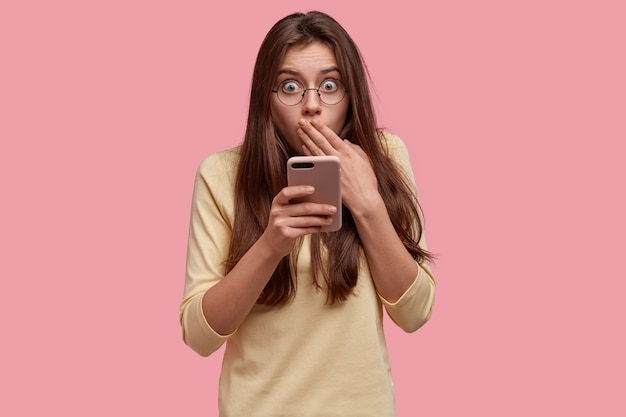 Giovane donna spaventata copre la bocca, prova paura, porta con sé un cellulare moderno, indossa gli occhiali, legge qualcosa di sorprendente su internet