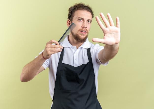 オリーブグリーンの背景に分離された停止ジェスチャーを示す制服を保持している櫛を身に着けている怖い若い男性の理髪師