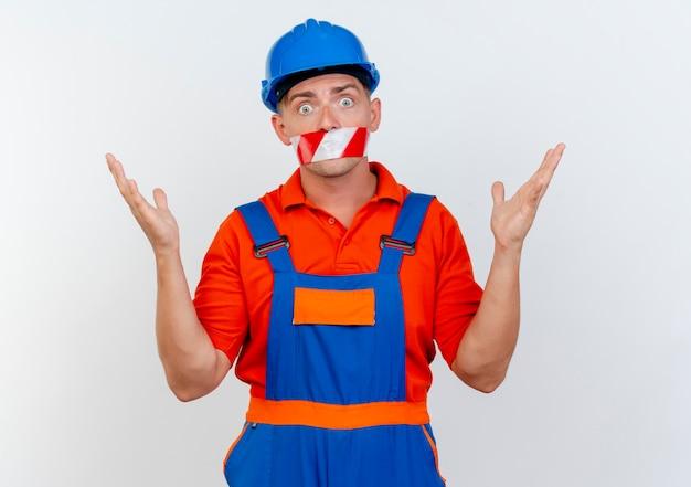 유니폼과 안전 헬멧을 쓰고 무서워하는 젊은 남성 빌더는 테이프로 입을 봉인하고 손을 펼칩니다.