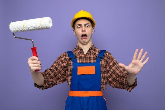Spaventato giovane costruttore maschio che indossa l'uniforme tenendo la spazzola a rullo