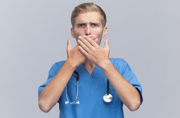 Spaventato il giovane medico maschio che indossa l'uniforme del medico con lo stetoscopio ha coperto la bocca con le mani isolate sulla parete bianca