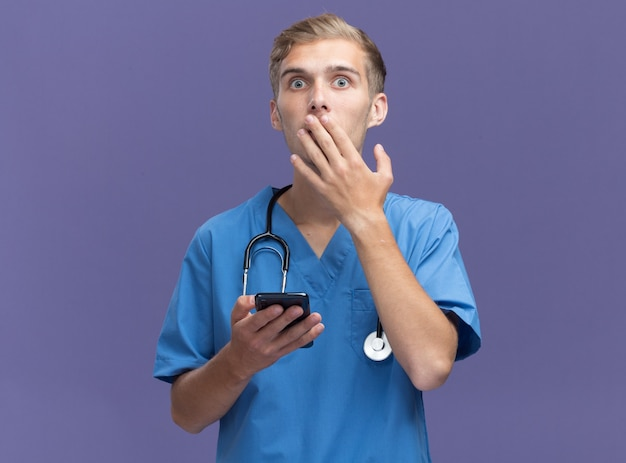 Spaventato giovane medico maschio indossa uniforme medico con lo stetoscopio che tiene il telefono e la bocca coperta con la mano isolata sulla parete blu
