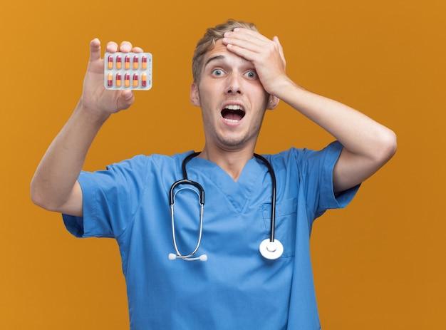 Spaventato giovane medico maschio che indossa l'uniforme del medico con lo stetoscopio che tiene le pillole mettendo la mano sulla testa isolata sulla parete arancione