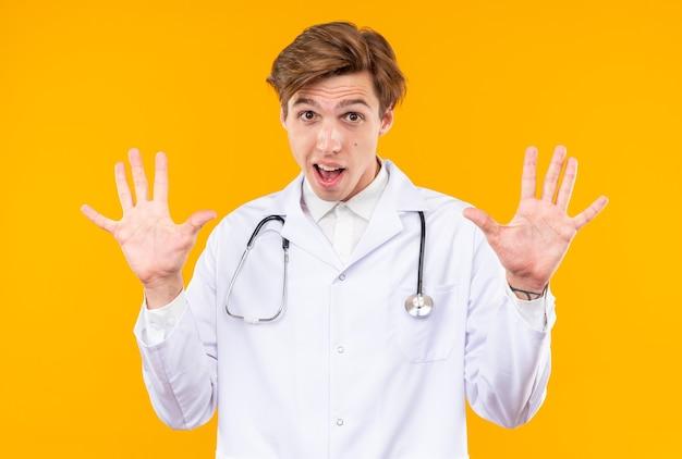 Испуганный молодой мужчина-врач в медицинском халате со стетоскопом показывает жест остановки, изолированный на оранжевой стене