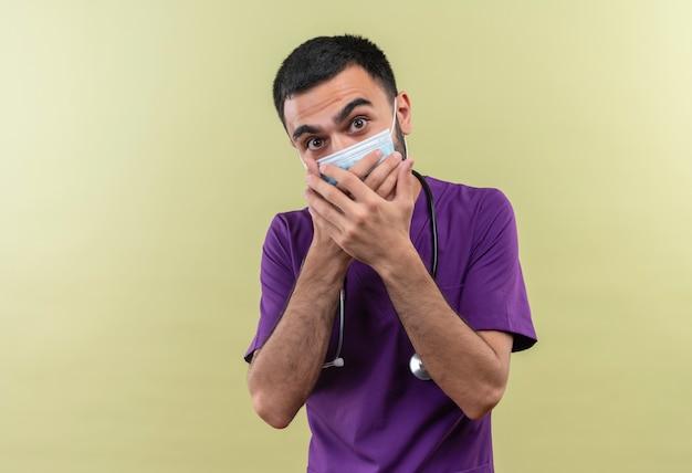 Spaventato il giovane medico maschio che indossa l'abbigliamento viola del chirurgo e la mascherina medica dello stetoscopio ha coperto la bocca con le mani su fondo verde isolato