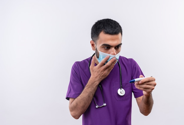 Spaventato giovane medico maschio indossa viola chirurgo abbigliamento e stetoscopio maschera medica guardando termometro in mano coperta bocca con la mano isolato su sfondo bianco