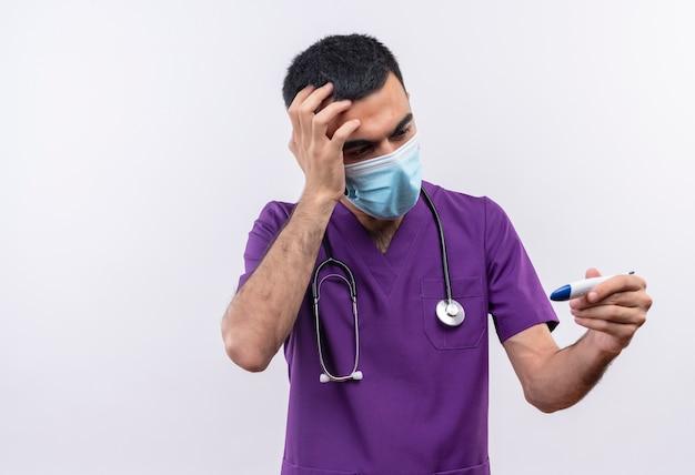 Spaventato giovane medico maschio indossa viola chirurgo abbigliamento e stetoscopio maschera medica mise la mano sulla fronte cercando di termometro in mano isolato su sfondo bianco