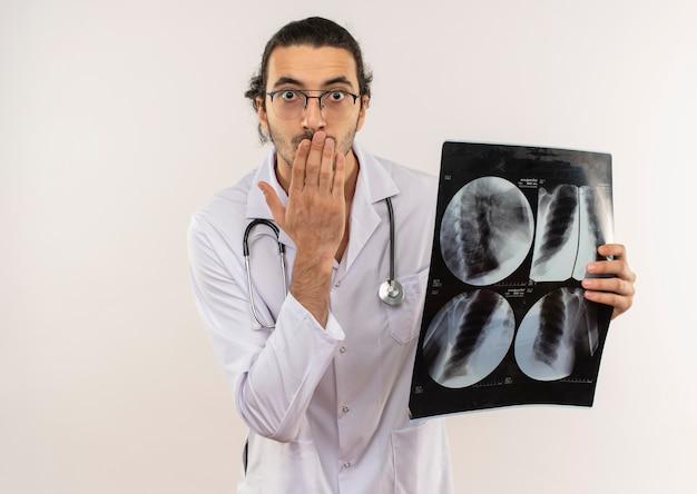 X線を保持し、コピースペースのある孤立した白い壁に手で口を覆った聴診器で白いローブを身に着けている光学メガネで怖い若い男性医師