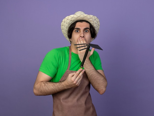 괭이 갈퀴를 들고 원예 모자를 쓰고 제복을 입은 무서워 젊은 남성 정원사는 손으로 입을 덮었습니다.