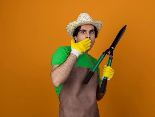 Scared young male gardener in uniform wearing gardening hat with gloves holding clippers covered mouth with hand