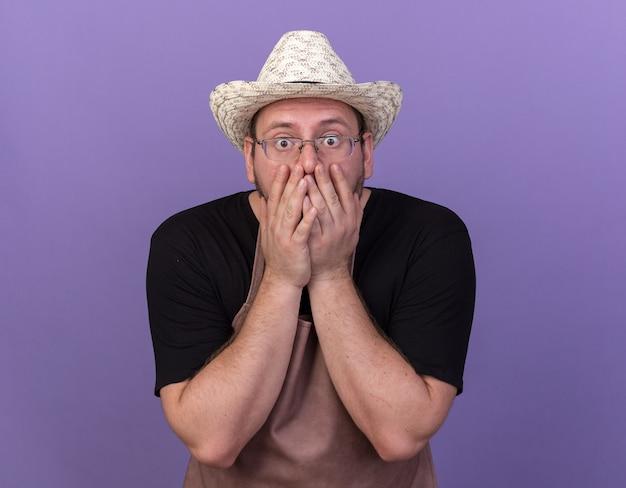 Il giovane giardiniere maschio spaventato che porta il cappello di giardinaggio ha coperto la bocca con le mani isolate sulla parete blu