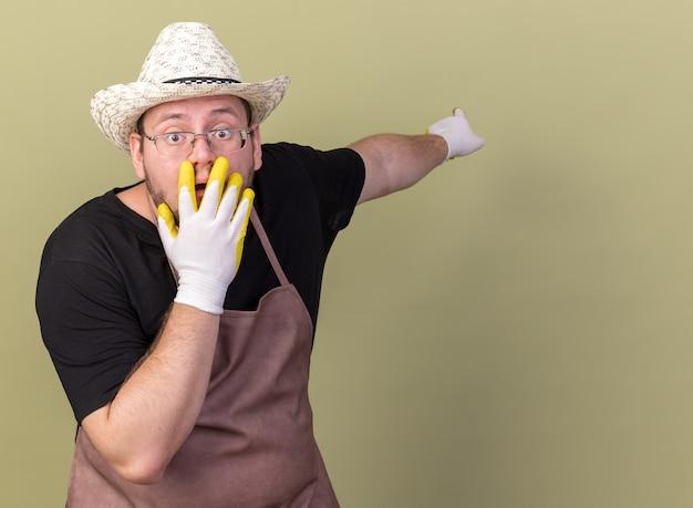Giovane giardiniere maschio spaventato che indossa guanti e cappello da giardinaggio indica dietro la bocca coperta con la mano isolata sulla parete verde oliva con lo spazio della copia