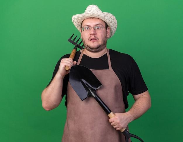 緑の壁に分離された肩に熊手を置くスペードを保持しているガーデニング帽子をかぶって怖い若い男性の庭師