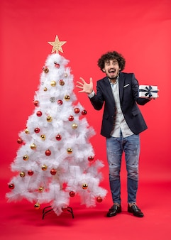 赤の右側に飾られた白いクリスマスツリーの近くに立って彼の贈り物を保持している怖い若い男