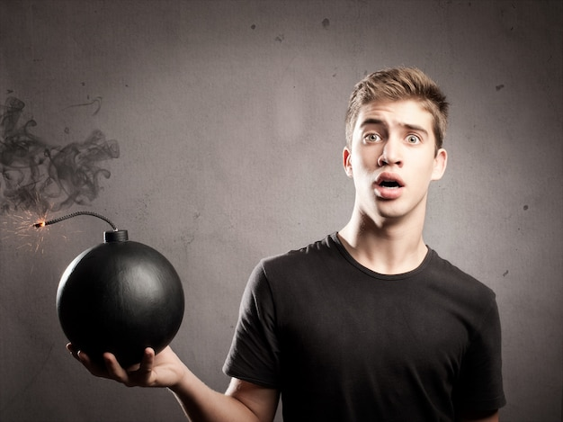 Scared young man holding an old-fashioned bomb