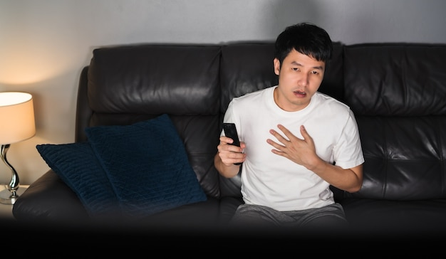Scared young man is watching horror movie tv on sofa at night