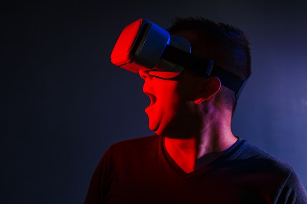 Scared young man in vr 3d glasses on dark background with red blue lighting
