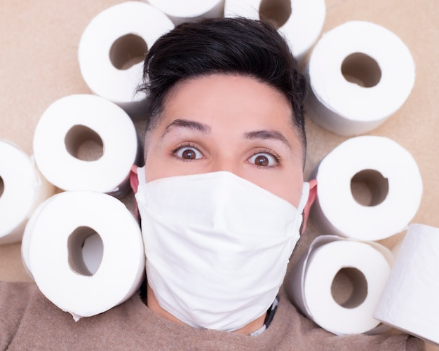 Scared young man with face mask on prevention surrounded by toilet paper.