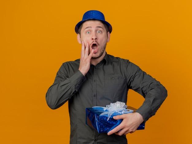 オレンジ色に分離された頬に手を置くギフトボックスを保持している青い帽子をかぶって怖い若いパーティー男