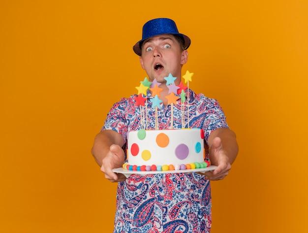 Ragazzo giovane spaventato del partito che porta il cappello blu che tiene fuori la torta isolata sull'arancia