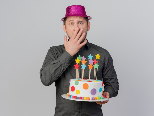 Scared young party guy wearing pink hat holding cake covered mouth with hand isolated on white background