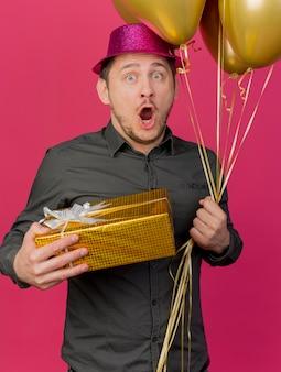 Ragazzo di partito giovane spaventato che indossa il cappello rosa che tiene confezione regalo con palloncini isolati su sfondo rosa