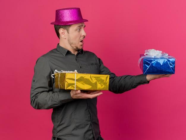 Ragazzo giovane spaventato del partito che porta il cappello rosa che tiene fuori il contenitore di regalo al lato isolato sul colore rosa