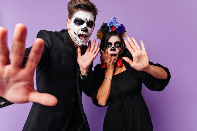 紫色の背景に一緒に立っているハロウィーンの服装で怖い若者。ムエルトスの衣装を着て浮気している熱狂的なヨーロッパのカップルの屋内写真。