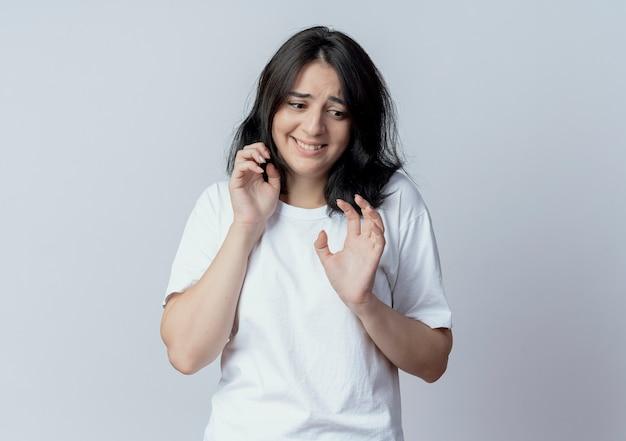 Испуганная молодая симпатичная кавказская девушка смотрит вниз и держит руки в воздухе, жестикулируя не изолированно на белом фоне с копией пространства