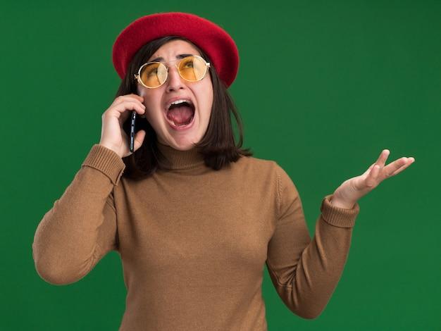 태양 안경에 베레모 모자를 쓰고 겁에 질린 젊은 백인 소녀가 복사 공간이 있는 녹색 벽에 고립되어 전화 통화