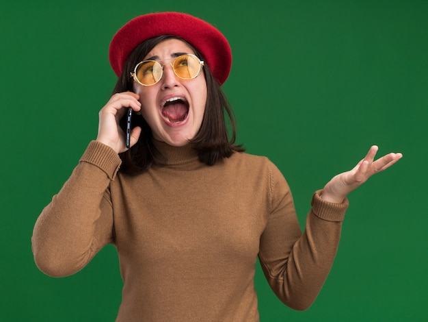 Giovane ragazza abbastanza caucasica spaventata con cappello berretto in occhiali da sole che parla al telefono guardando in alto isolato sulla parete verde con spazio copia