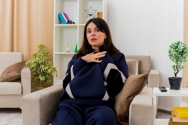 Spaventata giovane donna abbastanza caucasica seduta sulla poltrona nel soggiorno progettato mettendo le mani sul petto alla ricerca