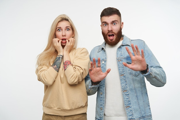 Scared young pretty couple rounding amazedly their blue eyes and raising emotionally hands while looking dazedly, isolated on white