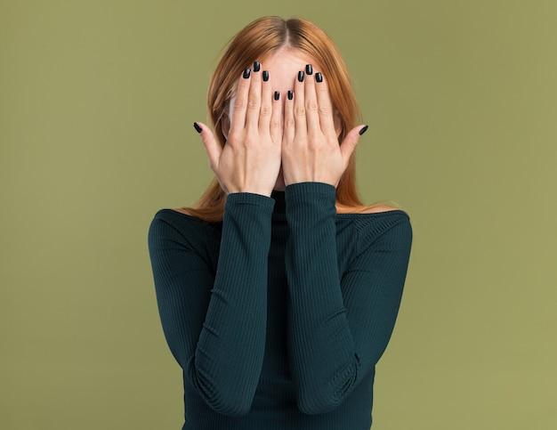 주근깨가 있는 겁에 질린 젊은 빨간 머리 생강 소녀는 복사 공간이 있는 올리브 녹색 벽에 격리된 손으로 얼굴을 덮습니다