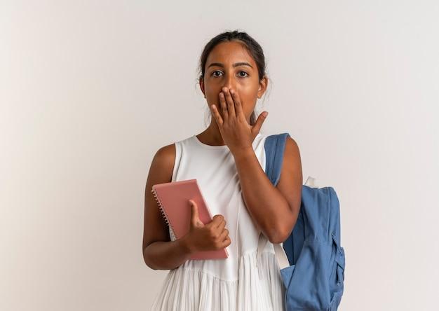 Испуганная молодая школьница в рюкзаке держит блокнот и прикрывает рот рукой
