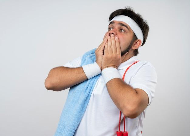 Испуганный молодой спортивный мужчина смотрит в сторону, носит повязку на голову и браслет с полотенцем и скакалкой на плече, покрытый рот, с руками, изолированными на белой стене