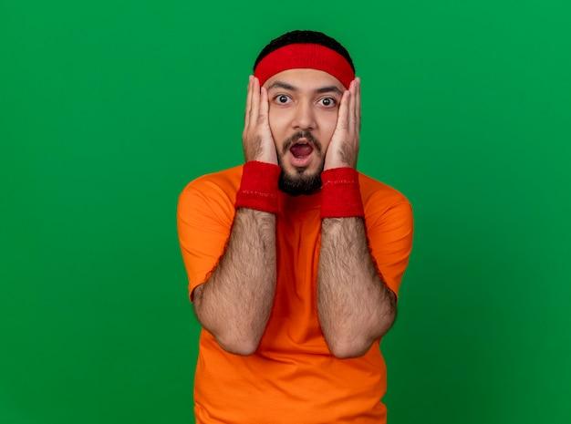 Испуганный молодой спортивный мужчина с головной повязкой и браслетом, положив руки на щеки, изолированные на зеленом фоне