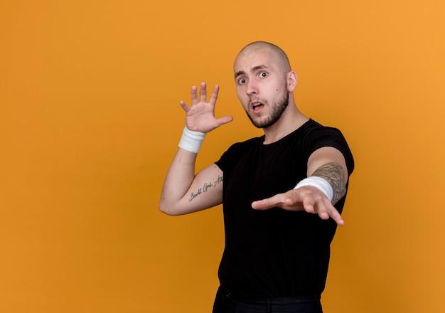 Spaventato il giovane uomo sportivo che indossa il braccialetto tendendo la mano isolata sulla parete arancione con lo spazio della copia