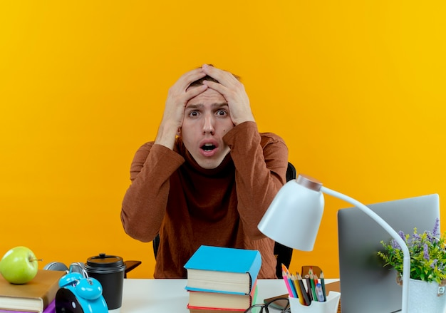 Scared young student boy sitting at desk with school tools grabbed head isolated on yellow wall