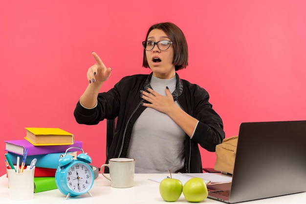 Ragazza giovane studente spaventato con gli occhiali seduto alla scrivania a fare i compiti guardando e indicando di lato con la mano sul petto isolato sulla parete rosa