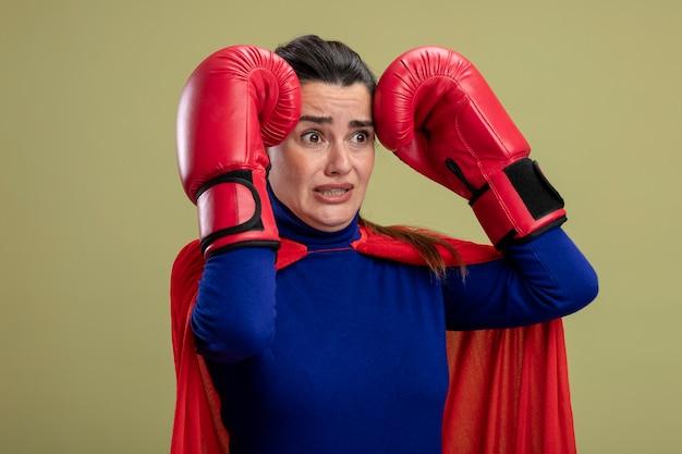 Spaventata giovane ragazza del supereroe guardando lato indossando guanti da boxe mettendo le mani sulla testa isolato su verde oliva