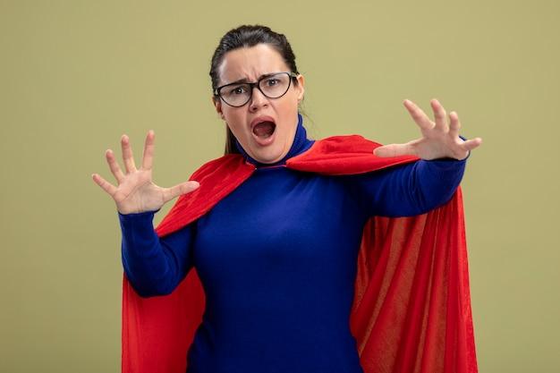 Испуганная молодая девушка супергероя в очках, раскинувшая руки, изолирована на оливково-зеленом